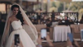 Όμορφη τοποθέτηση νυφών κατά τη διάρκεια των φίλων της που παίρνουν τις φωτογραφίες στο smartphone Ευτυχής γυναίκα στο άσπρο φόρε απόθεμα βίντεο