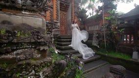 Όμορφη τοποθέτηση νυφών κοντά στο βουδιστικό ναό στο Μπαλί Να περπατήσει πλησίον κοντά ρομαντικός γάμος φιλμ μικρού μήκους