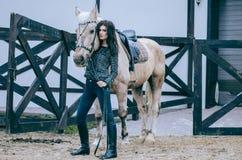 Όμορφη τοποθέτηση brunette με ένα άλογο το απόγευμα φθινοπώρου σε ένα αγρόκτημα χωρών Φωτογραφία τρόπου ζωής η μόδα σεντονιών βάζ στοκ φωτογραφία με δικαίωμα ελεύθερης χρήσης