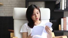 Όμορφη του πορτρέτου η νέα ασιατική γυναίκα χαλαρώνει το βιβλίο ανάγνωσης συνεδρίασης στο καθιστικό στο σπίτι, λογοτεχνία μελέτης απόθεμα βίντεο
