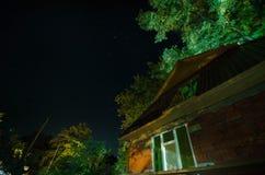 Όμορφη του χωριού οδός τοπίων με τα κτήρια και τα δέντρα και μεγάλη πανσέληνος στο νυχτερινό ουρανό Μεγάλος Καύκασος Στοκ Εικόνες
