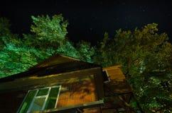 Όμορφη του χωριού οδός τοπίων με τα κτήρια και τα δέντρα και μεγάλη πανσέληνος στο νυχτερινό ουρανό Μεγάλος Καύκασος Στοκ φωτογραφία με δικαίωμα ελεύθερης χρήσης