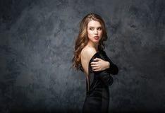 Όμορφη τρυφερή νέα γυναίκα στο μαύρο φόρεμα με την ανοικτή πλάτη στοκ φωτογραφία