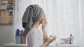 Όμορφη υγιής γυναίκα σε μια πετσέτα που βάζει την ενυδατική κρέμα στο πρόσωπο απόθεμα βίντεο