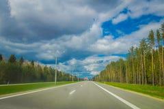 Όμορφη υπαίθρια άποψη της εθνικής οδού στον αερολιμένα του Μινσκ στο δραματικό κλίμα σύννεφων με τα δέντρα σε κάθε πλευρά Στοκ φωτογραφίες με δικαίωμα ελεύθερης χρήσης