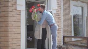 Όμορφη φέρνοντας ανθοδέσμη ατόμων των τουλιπών στο grandma Το γενειοφόρο άτομο που αγκαλιάζει τη γιαγιά του Χαμόγελο ανθρώπων Πρό απόθεμα βίντεο