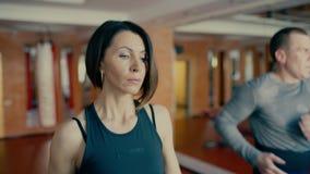Όμορφη φίλαθλη γυναίκα brunette των μέσων ετών που περπατά, που τρέχει treadmill στη γυμναστική workout 4 Κ φιλμ μικρού μήκους