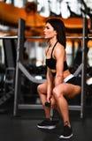 Όμορφη φίλαθλη προκλητική γυναίκα που κάνει τη στάση οκλαδόν workout στη γυμναστική στοκ φωτογραφίες