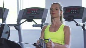 Όμορφη φίλαθλος που κάνει την καθισμένη άσκηση κωπηλασίας καλωδίων στη γυμναστική απόθεμα βίντεο