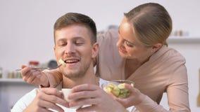 Όμορφη φίλη που ταΐζει στον όμορφο φίλο της με τη σαλάτα φρούτων την υγιή κατανάλωση απόθεμα βίντεο