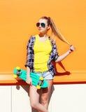 Όμορφη φθορά κοριτσιών μόδας γυαλιά ηλίου με skateboard πέρα από το ζωηρόχρωμο πορτοκάλι στοκ φωτογραφία