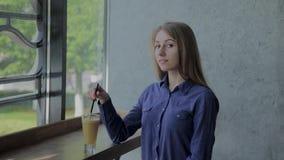 Όμορφη φρέσκια συνεδρίαση μήλων κοριτσιών ανακατώνοντας από το παράθυρο απόθεμα βίντεο
