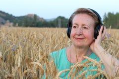 Όμορφη φυσική ώριμη γυναίκα με τα ακουστικά υπαίθρια Απόλαυση της μουσικής με το διάστημα αντιγράφων Στοκ Φωτογραφία