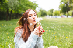 Όμορφη φυσώντας πικραλίδα κοριτσιών στο θερινό πάρκο Πράσινη όμορφη φύση χλόης Στοκ Εικόνες