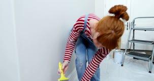 Όμορφη χαλάρωση γυναικών μετά από να χρωματίσει τον τοίχο 4k απόθεμα βίντεο