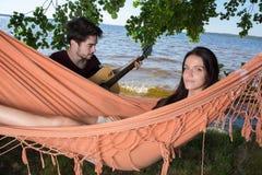 Όμορφη χαλάρωση κοριτσιών στην κιθάρα παιχνιδιού φίλων ακούσματος αιωρών Στοκ φωτογραφία με δικαίωμα ελεύθερης χρήσης