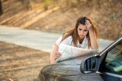 Όμορφη χαμένη γυναίκα που εξετάζει έναν χάρτη στην πλευρά του δρόμου στοκ φωτογραφία