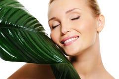 Όμορφη χαμογελώντας γυναίκα και φρέσκο πράσινο φύλλο Στοκ φωτογραφία με δικαίωμα ελεύθερης χρήσης