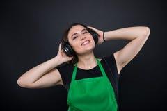 Όμορφη χαμογελώντας γυναίκα με την πράσινη μουσική ακούσματος ποδιών Στοκ Εικόνες