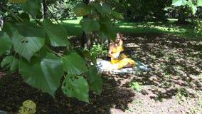 Όμορφη χαμογελώντας γυναίκα με το lap-top που κουβεντιάζει με τη χαλάρωση φίλων στο ηλιόλουστο πάρκο 4K φιλμ μικρού μήκους