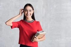 Όμορφη χαμογελώντας γυναίκα που κρατά τα σημειωματάρια Στοκ Φωτογραφία