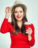 Όμορφη χαμογελώντας γυναίκα που φορά το κόκκινο πουλόβερ που κρατά τον κόκκινο καφέ γ Στοκ Εικόνες