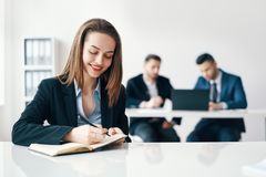 Όμορφη χαμογελώντας επιχειρησιακή γυναίκα που γράφει και που κάνει τις σημειώσεις στο σημειωματάριο στο σύγχρονο γραφείο στοκ φωτογραφία