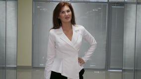 Όμορφη χαμογελώντας επιχειρησιακή γυναίκα που στέκεται στο κλίμα γραφείων φιλμ μικρού μήκους