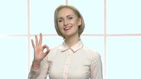 Όμορφη χαμογελώντας επιχειρησιακή κυρία που παρουσιάζει εντάξει σημάδι απόθεμα βίντεο