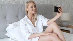 Όμορφη, χαμογελώντας μέση ηλικίας γυναίκα που κάνει selfie στην κρεβατοκάμαρα απόθεμα βίντεο