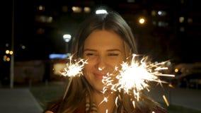 Όμορφη χαμογελώντας νέα γυναίκα που κρατά ένα sparkler city lights night scene Νέα χαμογελώντας εκμετάλλευση κοριτσιών sparkler σ Στοκ Εικόνα