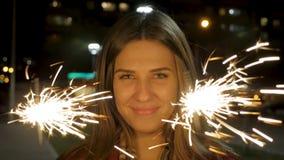 Όμορφη χαμογελώντας νέα γυναίκα που κρατά ένα sparkler city lights night scene Νέα χαμογελώντας εκμετάλλευση κοριτσιών sparkler σ Στοκ φωτογραφίες με δικαίωμα ελεύθερης χρήσης
