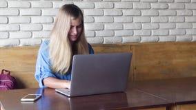 Όμορφη χαμογελώντας νέα γυναίκα που χρησιμοποιεί το lap-top της στον καφέ απόθεμα βίντεο