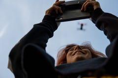 Όμορφη χαμογελώντας νέα κόκκινη επικεφαλής γυναίκα που χρησιμοποιεί τον κηφήνα Θολωμένο πέταγμα copter στον ουρανό και το ευτυχές στοκ φωτογραφίες