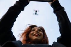 Όμορφη χαμογελώντας νέα κόκκινη επικεφαλής γυναίκα που χρησιμοποιεί τον κηφήνα Θολωμένο πέταγμα copter στον ουρανό και το ευτυχές στοκ εικόνες με δικαίωμα ελεύθερης χρήσης
