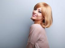 Όμορφη χαμογελώντας γυναίκα δοντιών με τα κοντά ξανθά μαλλιά που κοιτάζει happ στοκ φωτογραφία
