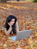 Όμορφη χαμογελώντας γυναίκα που βρίσκεται στο έδαφος με το lap-top Στοκ Εικόνες