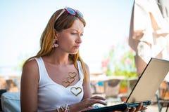 Όμορφη χαμογελώντας γυναίκα που εργάζεται στο lap-top Στοκ εικόνες με δικαίωμα ελεύθερης χρήσης