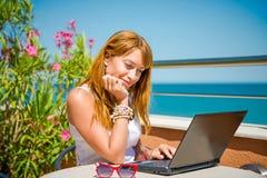 Όμορφη χαμογελώντας γυναίκα που εργάζεται στο lap-top Στοκ φωτογραφία με δικαίωμα ελεύθερης χρήσης