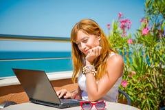 Όμορφη χαμογελώντας γυναίκα που εργάζεται στο lap-top Στοκ Φωτογραφίες