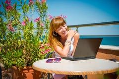 Όμορφη χαμογελώντας γυναίκα που εργάζεται στο lap-top Στοκ Φωτογραφία