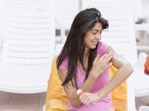 Όμορφη χαμογελώντας γυναίκα που εφαρμόζει την κρέμα ήλιος-προστασίας Στοκ Εικόνα
