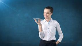 Όμορφη χαμογελώντας γυναίκα που κρατά έναν δίσκο και που εξετάζει σας Απομονωμένο υπόβαθρο στούντιο με το copyspace χρυσή ιδιοκτη Στοκ Εικόνες
