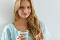 Όμορφη χαμογελώντας γυναίκα που παίρνει το χάπι βιταμινών Διαιτητικό συμπλήρωμα Στοκ Εικόνα