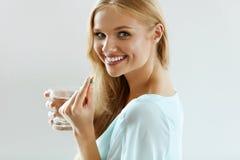 Όμορφη χαμογελώντας γυναίκα που παίρνει το χάπι βιταμινών Διαιτητικό συμπλήρωμα στοκ εικόνες με δικαίωμα ελεύθερης χρήσης