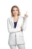 Όμορφη χαμογελώντας γυναίκα που παρουσιάζει δάχτυλο στο ελαφρύ υπόβαθρο Στοκ εικόνες με δικαίωμα ελεύθερης χρήσης