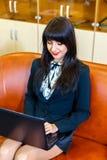 Όμορφη χαμογελώντας γυναίκα σε μια συνεδρίαση κοστουμιών στην αρχή στον ομο στοκ εικόνες
