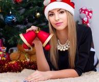 Όμορφη χαμογελώντας γυναίκα στο καπέλο santa με τα κουδούνια Χριστουγέννων στοκ φωτογραφίες