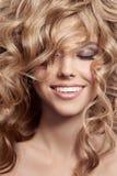 Όμορφη χαμογελώντας γυναίκα. Υγιής μακριά σγουρή τρίχα Στοκ Εικόνες