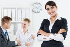 Όμορφη χαμογελώντας επιχειρησιακή γυναίκα στο κοστούμι που στέκεται με cro χεριών Στοκ Εικόνα